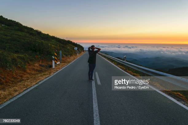 rear view of woman on road against sky during sunset - monchique stock pictures, royalty-free photos & images