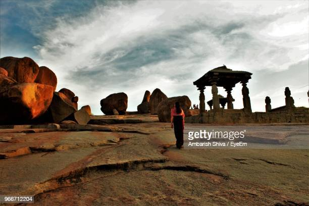 rear view of woman on rocky landscape - karnataka stock pictures, royalty-free photos & images