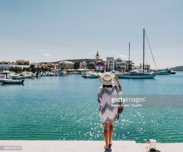rear view of woman on sea shore looking at town, marina, boats. - croatia stock pictures, royalty-free photos & images