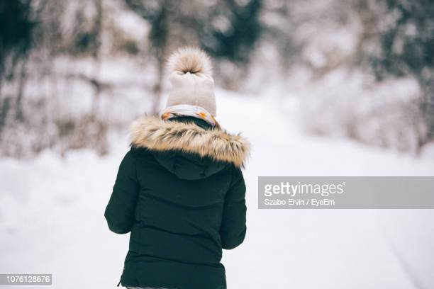rear view of woman on snow covered field - winter coat stock pictures, royalty-free photos & images