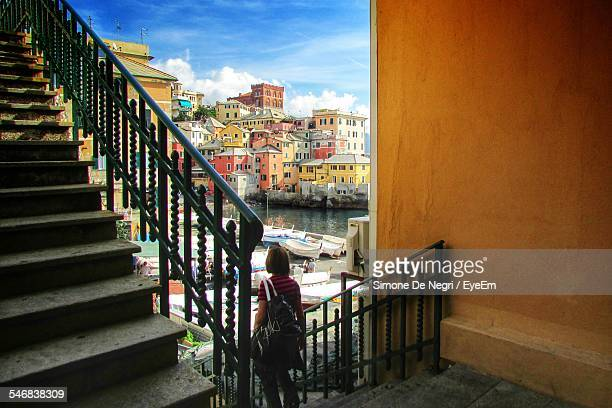 Rear View Of Woman On Staircase Of Harbor Against Cityscape And Sky