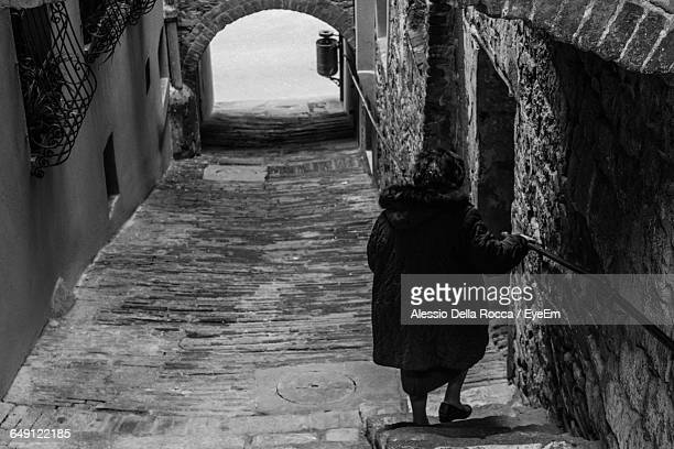 Rear View Of Woman On Steps In Old Town