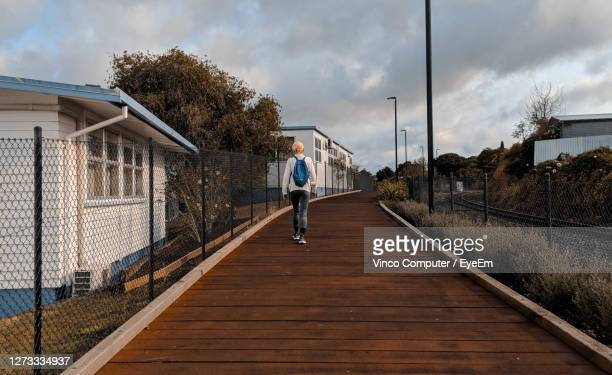rear view of woman on walkway against sky - whangarei heads stock pictures, royalty-free photos & images
