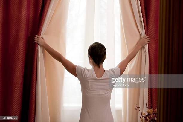rear view of woman opening curtains - closing stock photos and pictures