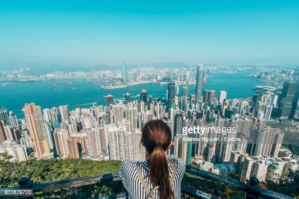 rear view of woman over cityscape against sky - hong kong stock pictures, royalty-free photos & images