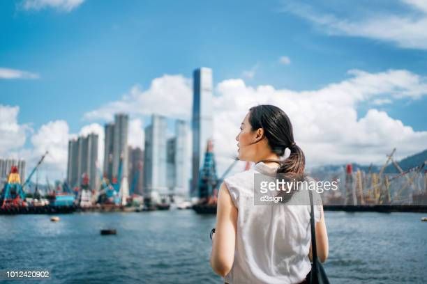 rear view of woman overlooking busy and energetic cityscape of hong kong against blue sky - reportaje imágenes stock pictures, royalty-free photos & images