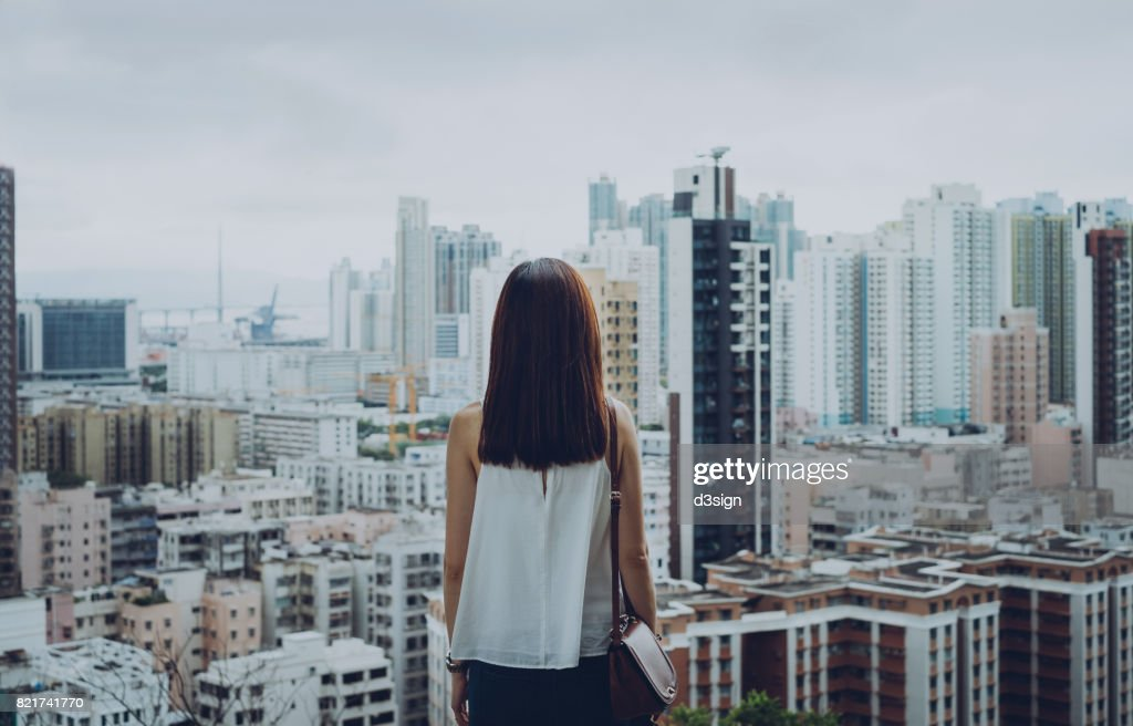 Rear view of woman overlooking busy and energetic cityscape of Hong Kong : Stock-Foto