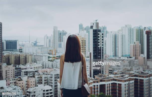 rear view of woman overlooking busy and energetic cityscape of hong kong - decisions imagens e fotografias de stock