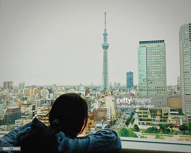 Rear View Of Woman Overlooking Cityscape