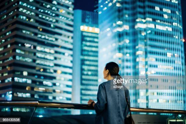 Rear view of woman overlooking iconic cityscape of Hong Kong at night