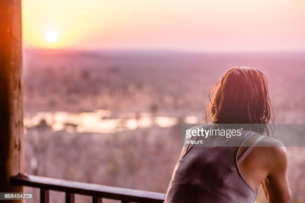 Rear view of Woman overlooking waterhole at sunset