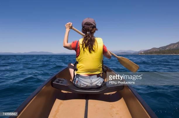 Rear view of woman paddling canoe