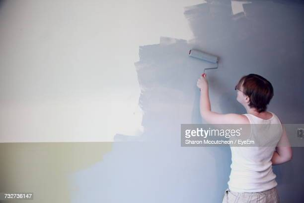 Rear View Of Woman Painting Wall In Living Room At Home