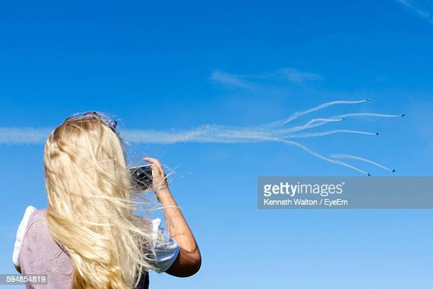 Rear View Of Woman Photographing Airshow