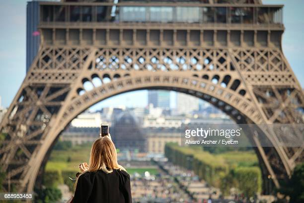 Rear View Of Woman Photographing Eiffel Tower