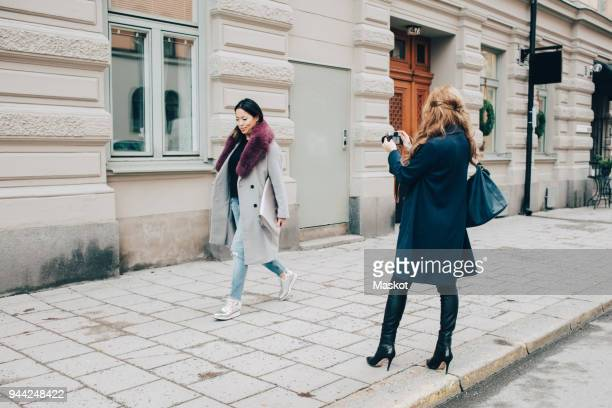 rear view of woman photographing female friend walking on sidewalk against building in city - overcoat stock pictures, royalty-free photos & images