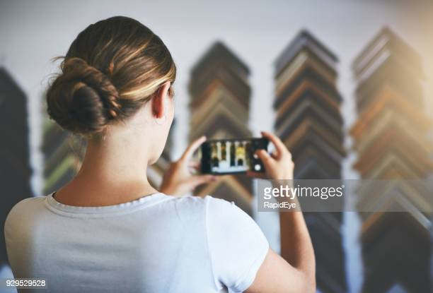 Rear view of woman photographing frames in store