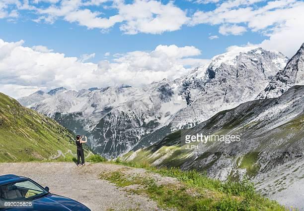 Rear view of woman photographing mountain, Passo di Stelvio, Stelvio, Italy