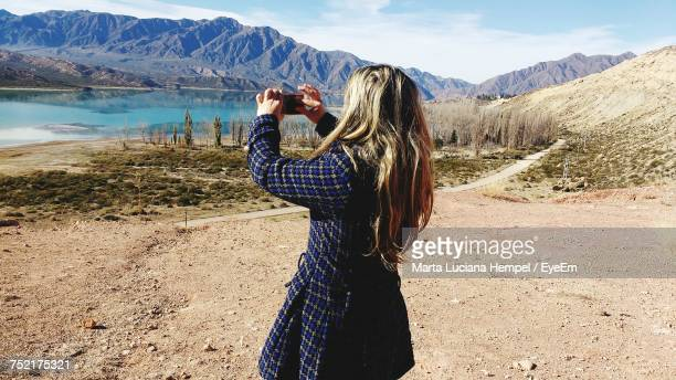 Rear View Of Woman Photographing Mountain Through Smart Phone On Sunny Day