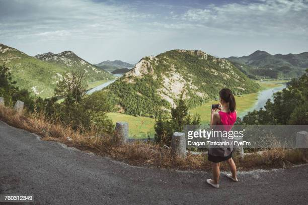 Rear View Of Woman Photographing Mountains Through Mobile Phone While Standing On Road