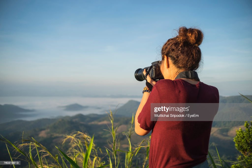 Rear View Of Woman Photographing On Field Against Sky : Foto de stock