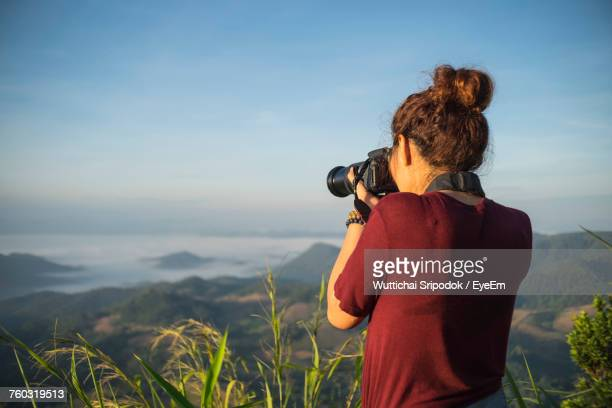 rear view of woman photographing on field against sky - fotograf stock-fotos und bilder