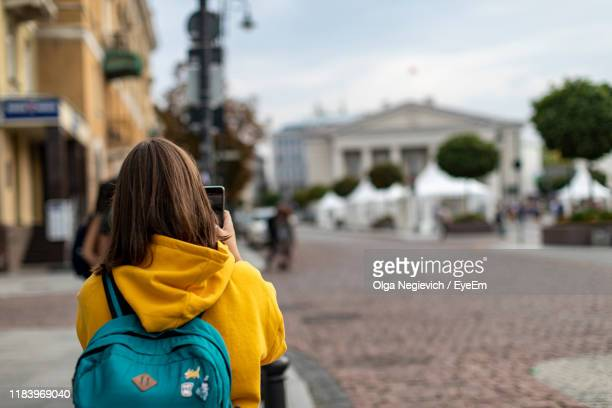 rear view of woman photographing on footpath against buildings - vilnius stock pictures, royalty-free photos & images
