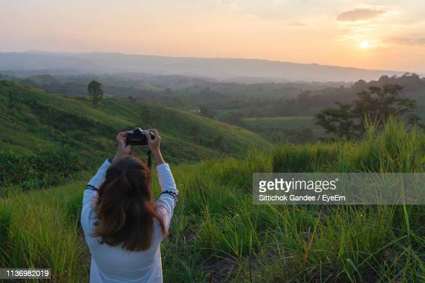 Rear View Of Woman Photographing On Landscape Against Sky During Sunset