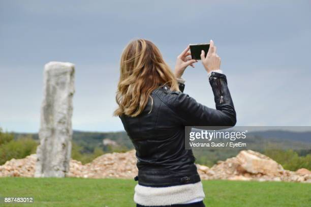 Rear View Of Woman Photographing Through Camera While Standing On Field