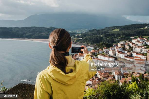 rear view of woman photographing village through mobile phone during vacations - selective focus imagens e fotografias de stock