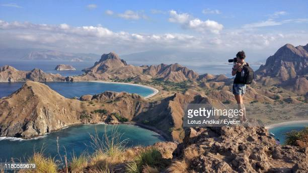 rear view of woman photographing while standing on rock against sky - east nusa tenggara stock pictures, royalty-free photos & images