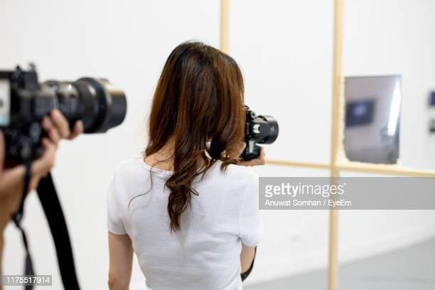 rear view of woman photographing with camera against wall - anuwat somhan stock photos and pictures