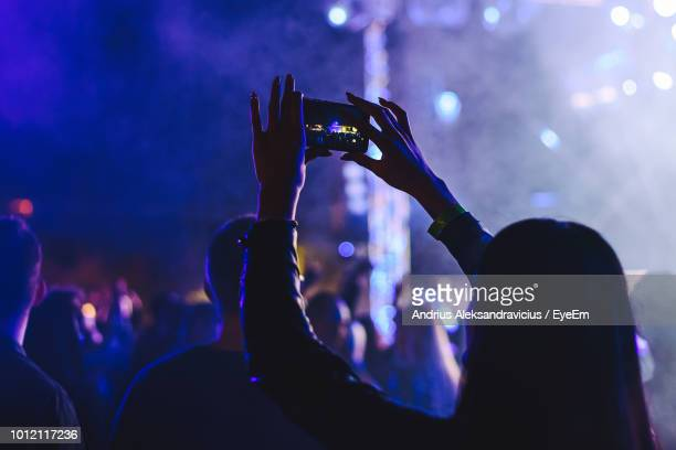 rear view of woman photographing with smart phone at music concert - 写真を撮る ストックフォトと画像