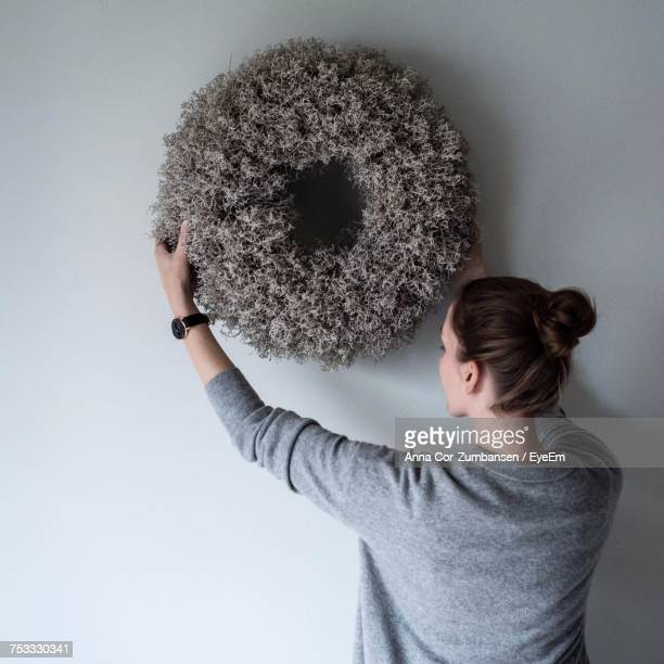 Rear View Of Woman Placing Wreath Decoration On Wall At Home