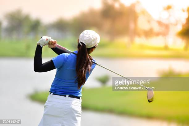 Rear View Of Woman Playing Golf