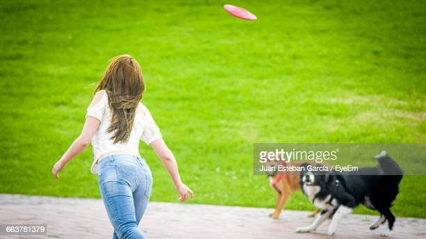 Rear View Of Woman Playing Plastic Disc With Dogs In Park