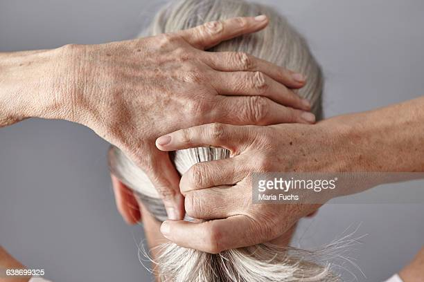 rear view of woman pulling back gray hair into ponytail - haar naar achteren stockfoto's en -beelden