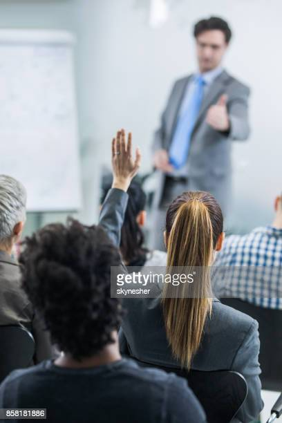 Rear view of woman raising a hand to ask the question while attending business seminar.