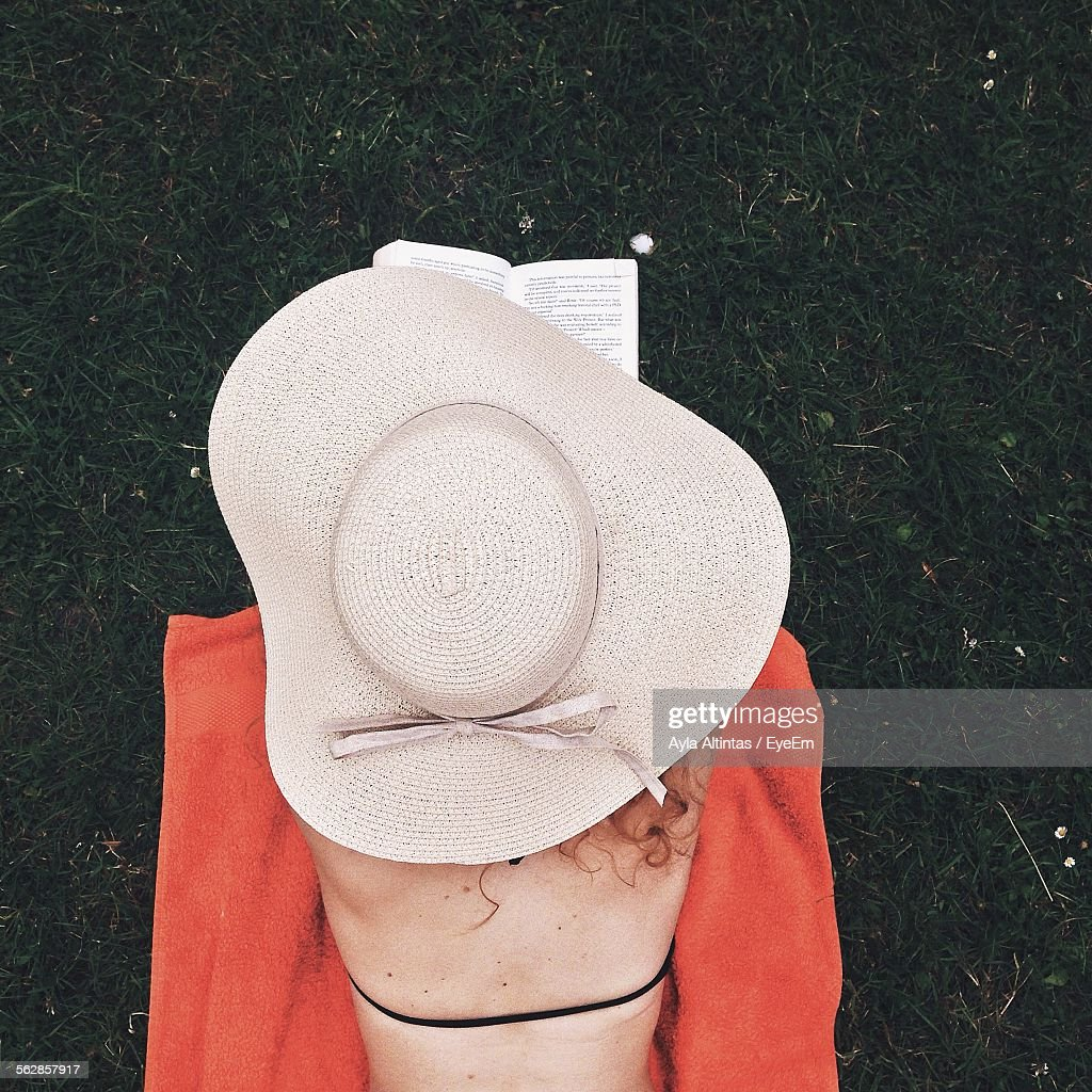 Rear View Of Woman Reading Book While Lying On Beach : Stock Photo