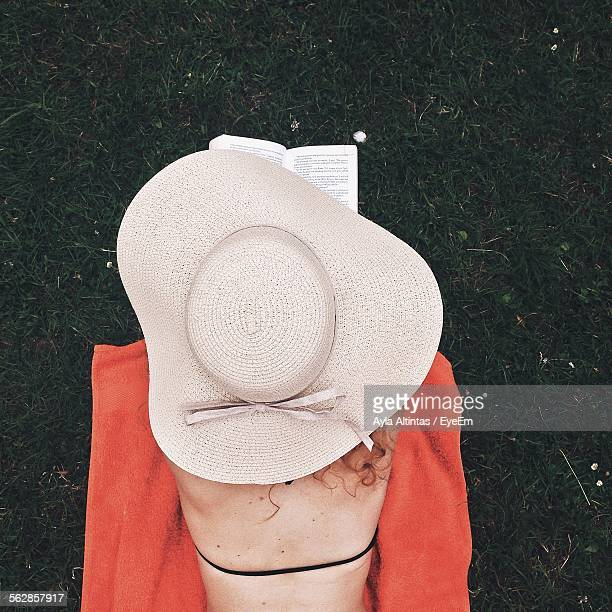 Rear View Of Woman Reading Book While Lying On Beach