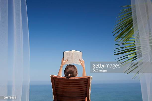 Rear view of woman reading book while sitting on deck chair