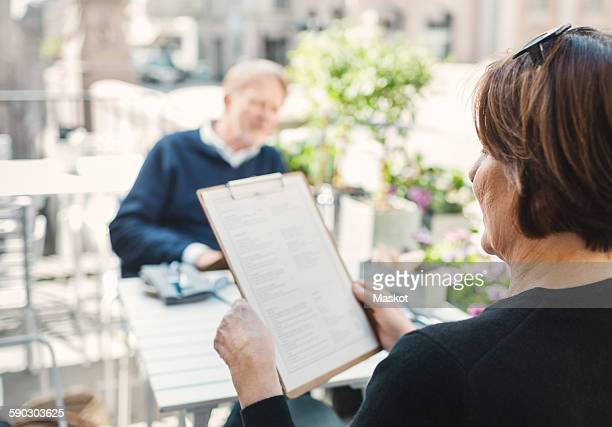 Rear view of woman reading menu while man sitting at sidewalk cafe