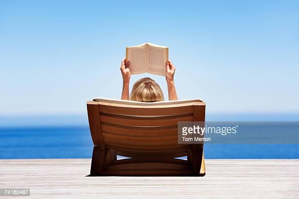 Vista posterior de lectura de mujer en silla de madera al aire libre