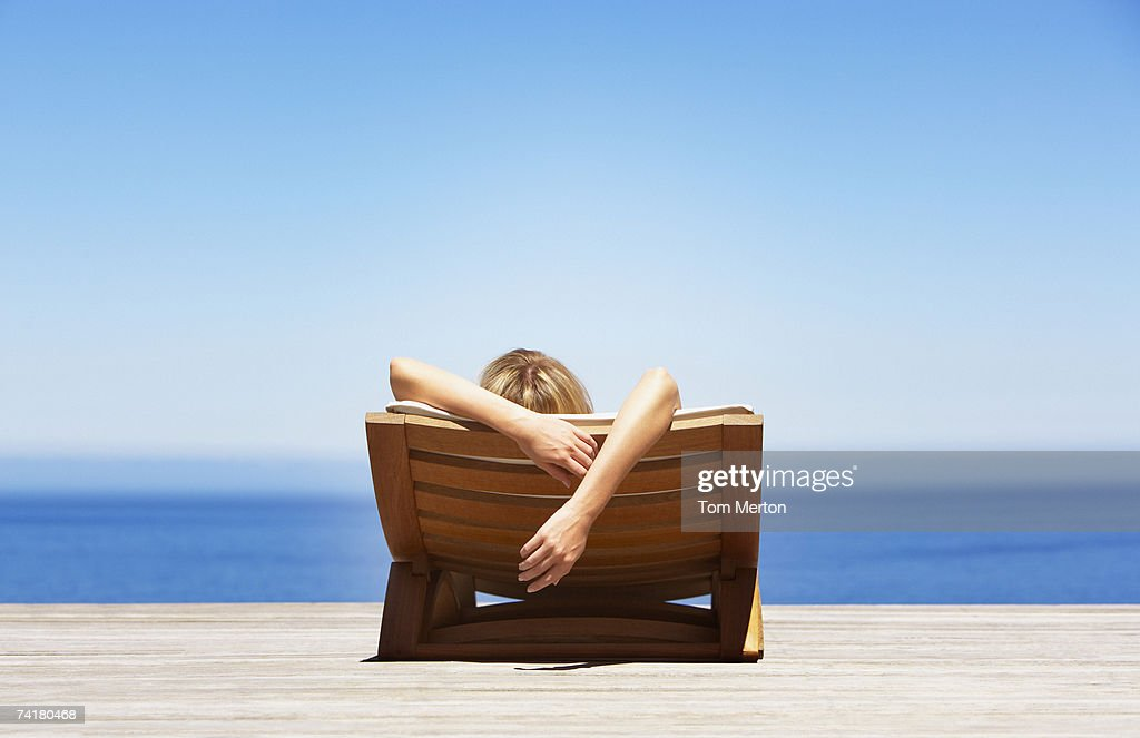 Rear view of woman reclining on folding chair outdoors : Stock Photo