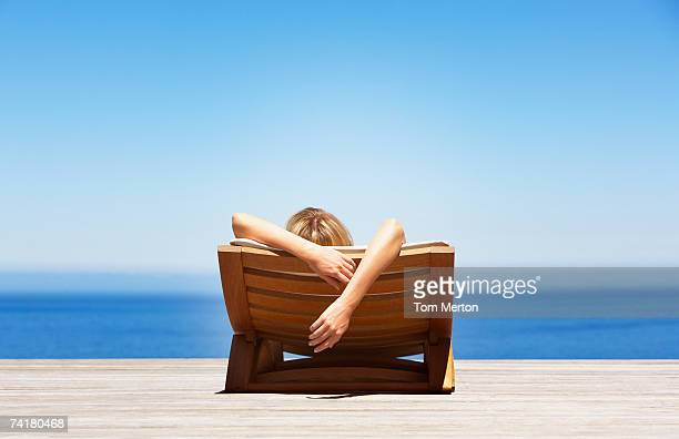rear view of woman reclining on folding chair outdoors - outdoor chair stock pictures, royalty-free photos & images