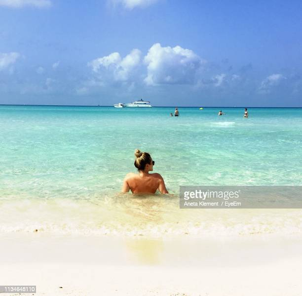 Rear View Of Woman Relaxing At Beach
