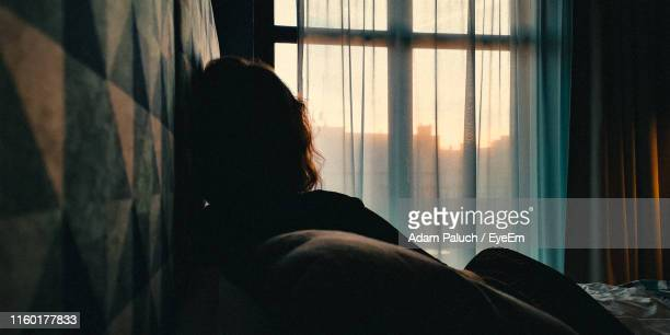rear view of woman relaxing on bed at home - looking at view foto e immagini stock