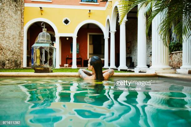 Rear view of woman relaxing on edge of pool in outdoor spa
