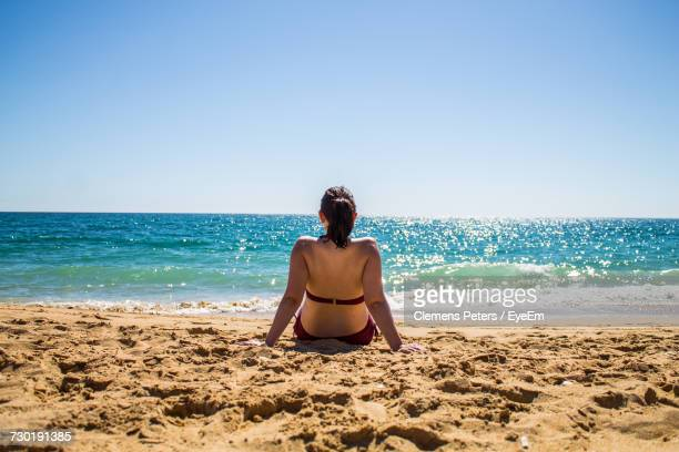 Rear View Of Woman Relaxing On Shore During Sunny Day