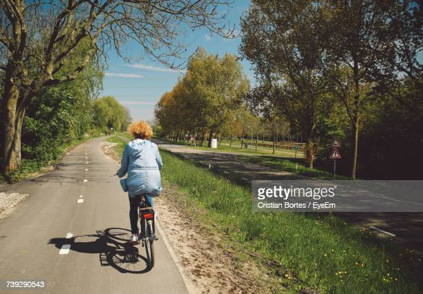 Rear View Of Woman Riding Bicycle During Sunny Day